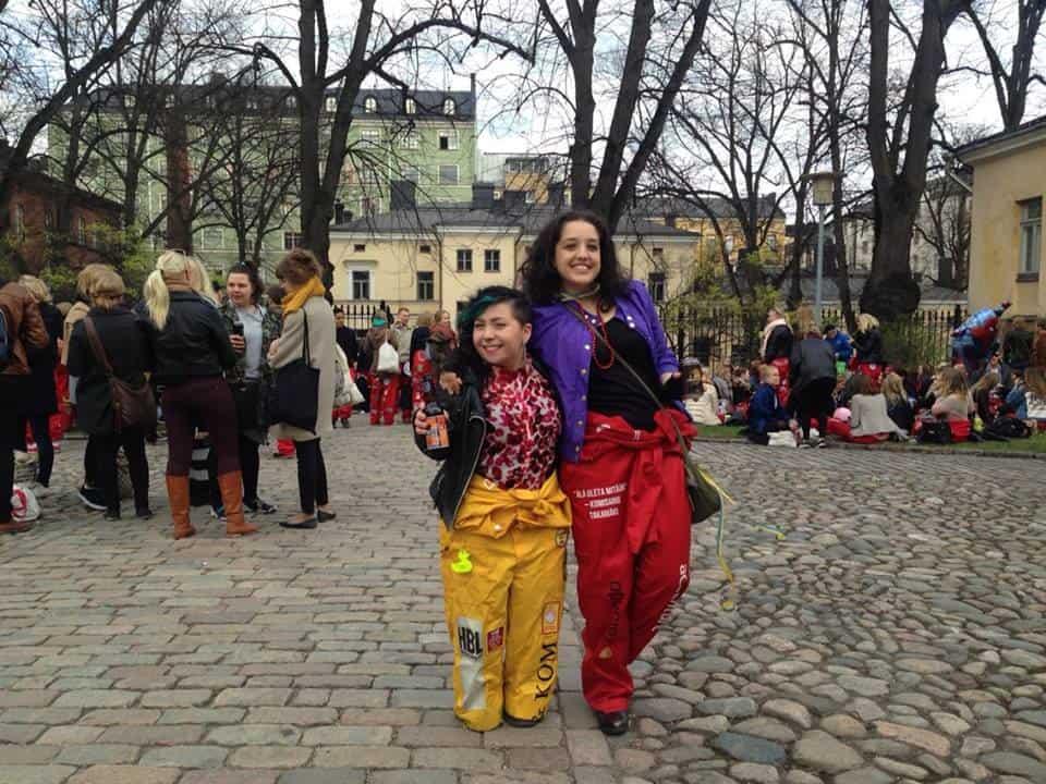 Ana (de vermelho) e uma amiga com os típicos macacões que os estudantes usam em eventos da universidade